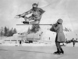 Der Trickeislaeufer Phil Taylor bei einem Sprung ueber einen Stock, um 1935