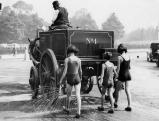 Kinder kuehlen sich  hinter einem Reinigungsfahrzeug ab, 1932