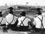 Zuschauer in bayerischer Tracht blicken vom Olympiaberg auf das Olympiastadion