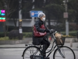 A cyclist wears a mask ride on a road, 2013