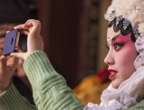 A Chinese opera artist uses her iphone at a performance in a temple, 2011