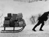 Postbote  traegt seine Pakete per Rodelschlitten aus, 1936