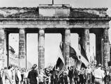 Demonstrierende Arbeiter ziehen mit deutschen Fahnen durch das Brandenburger Tor