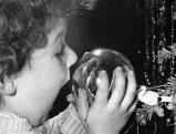 Kind erfreut sich am Spiegelbild in der Christbaumkugel, 50er Jahre