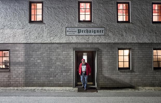 """Ein Mitglied des FC-Bayern-Fanclubs """"Red Bulls Taubenbach"""" überquert, von der Jahreshauptversammlung des Clubs kommend, das Gasthaus """"Pechaigner"""" in Noppling im Rottal, Niederbayern."""