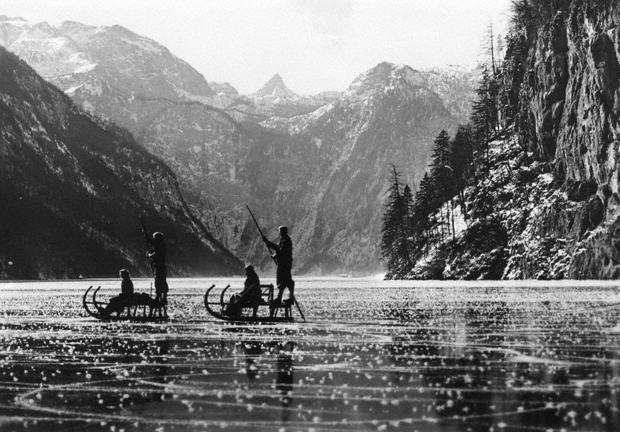 Menschen mit Schlitten auf dem zugefrorenen Königssee.