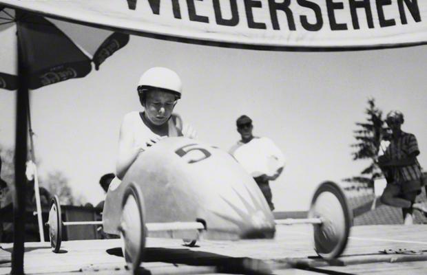 Junger Rennfahrer kneift die Augen beim Start des Augsburger Seifenkisten-Rennens am Rosenaustadion am 7. Juli 1957 zusammen. Seit dem Jahr 1948 engagierte sich die Adam Opel AG in Rüsselsheim als Sponsor für den Sport und verbreitete das amerikanische Soap-Box-Derby in Deutschland als 'Seifenkisten-Rennen für Deutschland'. Junge amerikanische Soldaten der Jugendorganisation der US-Militärverwaltung in Deutschland German Youth Activities (GYA) unterstützten die deutschen Kinder beim Erlernen des nötigen Know-hows.
