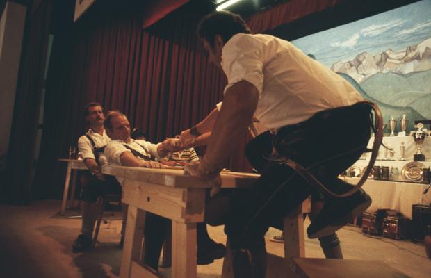 Männer versuchen beim Fingerhakeln den Gegner über den Tisch zu ziehen.