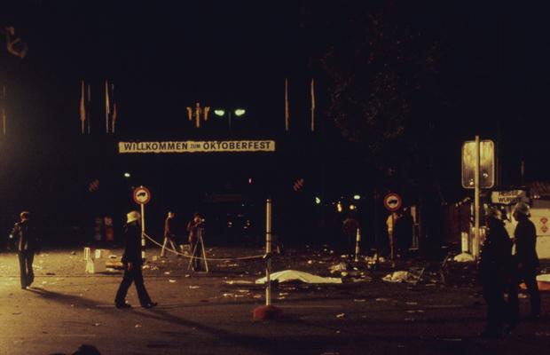 """Tatort des Oktoberfestattentats in München. Auf dem Schild im Hintergrund steht: """"Willkommen auf dem Oktoberfest""""."""