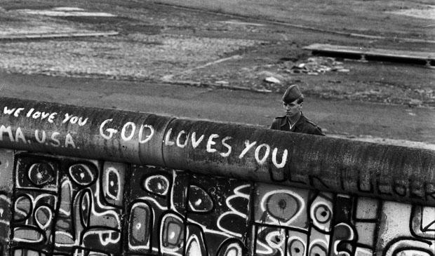 Berlin-City / Mitte / DDR / 6 / 1988 Potsdamer Platz: DDR-Grenzer schauen nach Westberlin. Dort haben junge Leute ein Stueck Niemandsland besetzt. Es liegt im Westen gehoert aber zum Osten. Die Westberliner Polizei ist gerade dabei zu raeumen. Der DDR-Grenzer weiss nicht, was auf der West-Seite der Mauer steht: -God loves you- // DDR-Mauer / Geschichte / Kommunismus / DDR-Staat