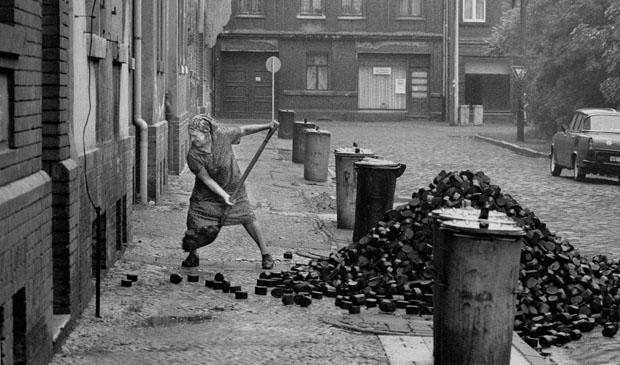 Sachsen-Anhalt / DDR-Land/ November 1989 Bitterfeld, eine alte Frau schaufelt Braunkohlen-Briketts in den Keller. In der DDR war es ueblich, den Kunden die Kohlen vor das Haus zu schuetten. Wohnsiedlung am Eisenbahn-Gelaende. // Menschen / Energie / Bundeslaender / Frauen