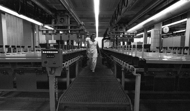 Berlin / Kreuzberg / 17.10.1980DeTeWe: In dem Betrieb werden Schaltschraenke fuer die Post hergestellt. Die Frauen produzieren Teile in der Vorfertigung. In der naechsten Generation der Technik werden diese Arbeiten von Automaten gemacht.Frau an der Galvanik. In den Reihen von Chemikalien-Baedern werden Leiterplaten geaetzt. Die Frau legt die Platten auf Transport-Baender.// Frauen-Arbeit / Industrie-Geschichte /