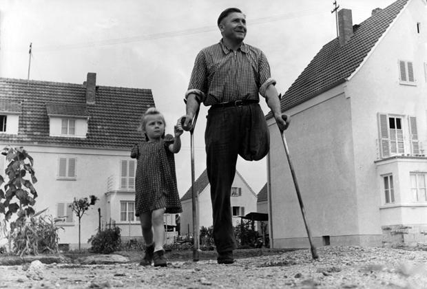 Ein Kriegsinvalide mit seiner ebenfalls kriegsversehrten Tochter in einer Neubausiedlung nach dem Zweiten Weltkrieg.