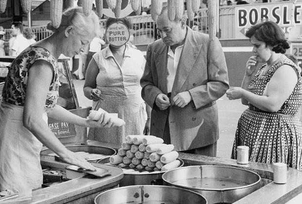 Eine Verkäuferin einer Imbissbude auf Coney Island verkauft ihren Kunden Maiskolben mit Butter.