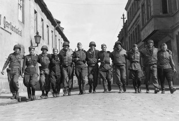 US-amerikanische und sowjetische Soldaten marschieren Arm in Arm durch Torgau nach dem sowjetisch-amerikanischen Aufeinandertreffen an der Elbe.