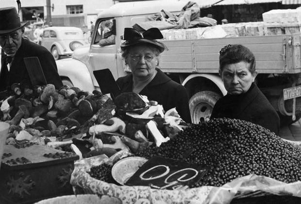 Ein Mann und zwei Frauen beim Bummeln und Schauen auf dem Viktualienmarkt in München, 1952