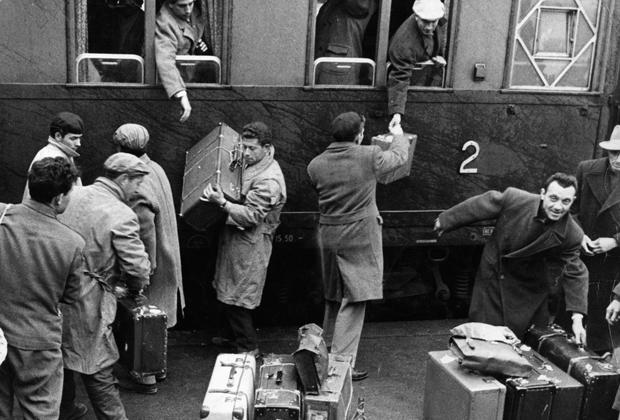 Italienische Gastarbeiter beim ausladen ihres Gepäcks aus dem Zug.