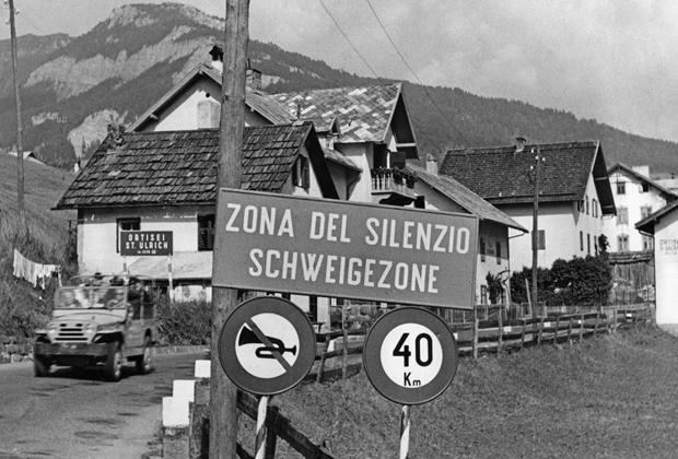 """Zweisprachiges Schild am Ortseingang St. Ulrich-Ortisei in Südtirol. Auf dem Schild steht """"Zona del Silenzio"""" (italienisch) und """"Schweigezone"""" (deutsch). Undatierte Aufnahme, vermutlich in den 1970er Jahren."""