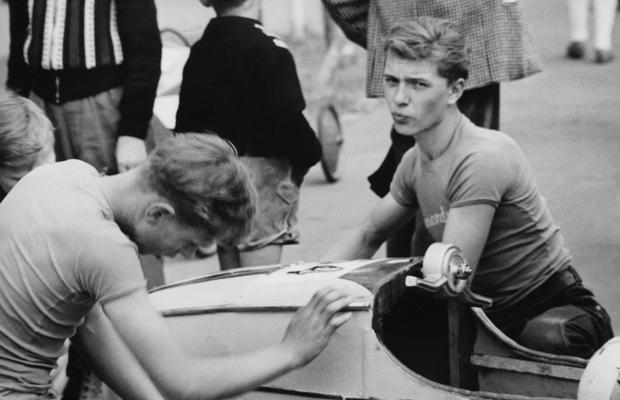 Zwei junge Männer feilen an einer Seifenkiste im Fahrerlager des Augsburger Seifenkisten-Rennens am Rosenaustadion am 22. Juni 1958. Seit dem Jahr 1948 engagierte sich die Adam Opel AG in Rüsselsheim als Sponsor für den Sport und verbreitete das amerikanische Soap-Box-Derby in Deutschland als 'Seifenkisten-Rennen für Deutschland'. Junge amerikanische Soldaten der Jugendorganisation der US-Militärverwaltung in Deutschland German Youth Activities (GYA) unterstützten die deutschen Kinder beim Erlernen des nötigen Know-hows.