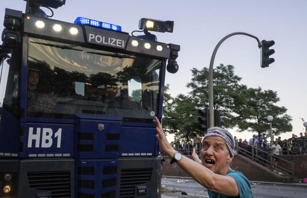 Ein Demonstrantin stellt sich alleine einem Wasserwerfer entgegen.
