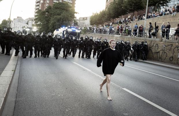 Ein Demonstrantin tut so, als ob sie eine Gruppe Polizisten anführt.