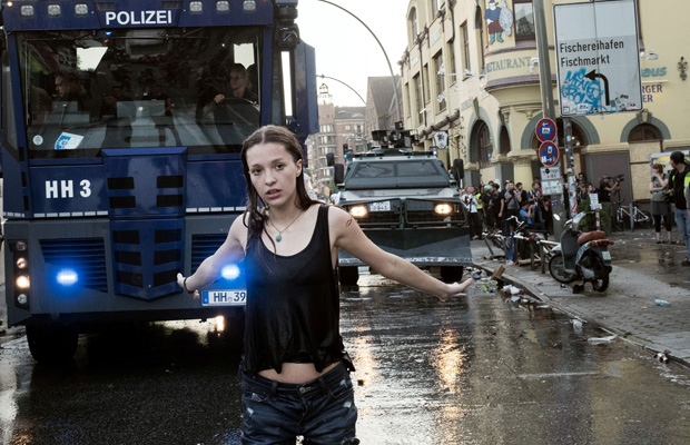 Ein Demonstrantin stellt sich Wasserwerfer der Polizei entgegen.