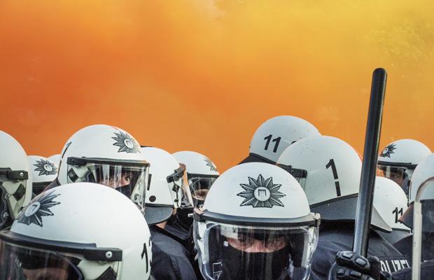 Eine Gruppe Polizisten im Rauch mehrerer Bengalos.