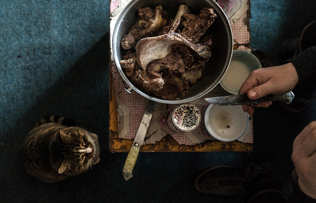 Traditionelles mongolisches Essen. Gekochtes Rind oder Schafsfleisch mit Salz und dazu Pferdemilchschnaps. Aus Gil Bartz' Fotoreportage 'We Won?t Die Sleeping'. Gil Bartz: ''We won?t die sleeping' represents my on-going photo project telling the story of former Sowjet countries. This episode is about Mongolia, concentrating on the nomadic life. The name-giving did not happen by chance.`We won?t die sleeping ? also is a very popular saying in Mongolia, strongly expressing the nature of this people. The big contrast between tradition and modern world with its progress is also taking its toll on the Nomads, forcing them to leave their habitual life behind to settle down near the cities. In the beginning of 2019 I travelled to north and south Mongolia to document the every-day life of some nomadic families.'