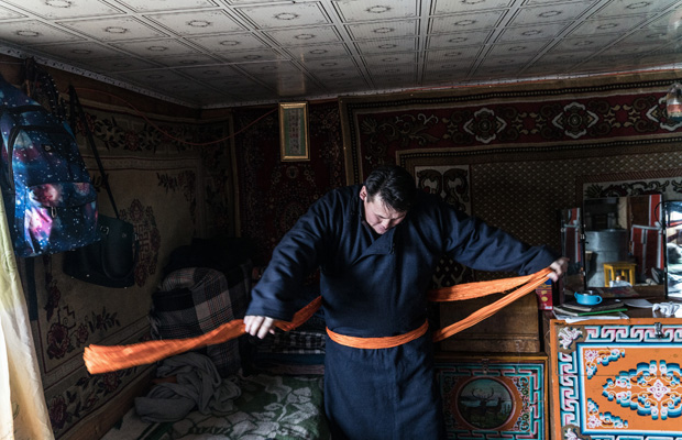 Ein Mann zieht einen Deel an. Der Deel ist ein traditionelles mongolisches Gewand. Aus Gil Bartz' Fotoreportage 'We Won?t Die Sleeping'. Gil Bartz: ''We won?t die sleeping' represents my on-going photo project telling the story of former Sowjet countries. This episode is about Mongolia, concentrating on the nomadic life. The name-giving did not happen by chance.`We won?t die sleeping ? also is a very popular saying in Mongolia, strongly expressing the nature of this people. The big contrast between tradition and modern world with its progress is also taking its toll on the Nomads, forcing them to leave their habitual life behind to settle down near the cities. In the beginning of 2019 I travelled to north and south Mongolia to document the every-day life of some nomadic families.'