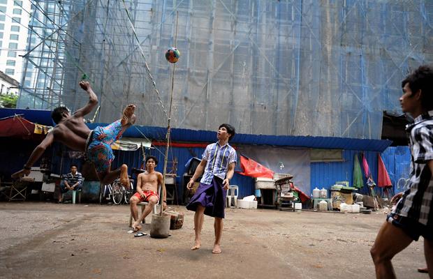 In einer Seitenstraße im Zentrum der birmanischen Hauptstadt Rangun (Yangon) spielen junge, birmanische Männer Takraw, 22. September, 2013. Dabei handelt es sich um eine sehr beliebte asiatische Ballsportart, die in Birma (Myanmar) auch unter dem Namen Chin Lone bekannt ist. Zwei Mannschaften aus jeweils drei Spielern versuchen mit maximal drei Berührungen den Ball aus Hartplastik über das Netz in das Spielfeld des Gegners zu schlagen.