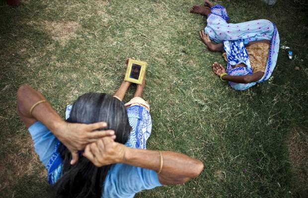 Eine indische witwe sitzt im Garten und kämmt ihre Haare, während eine andere Frau neben ihr liegt, am 7. Juni 2013 in Vrindavan, Indien.