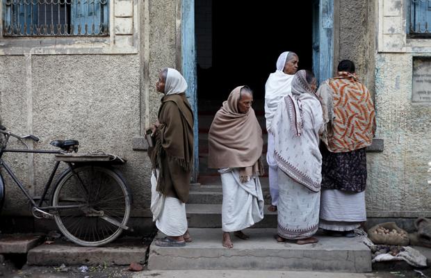 Indische Frauen (Witwen) stehen neugierig am EIngang eines Hauses in Vrindavan, Indien, am 8. Dezember 2011.