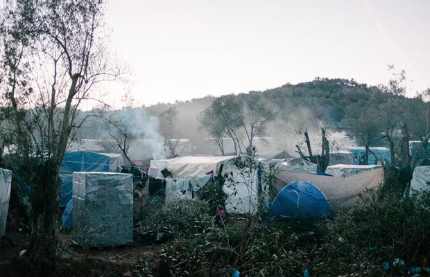 Blick über wildes Hüttenlager im Sonnenuntergang. - Moria ist das größte Lager für Geflüchtete in Europa. Auf der griechischen Ägäisinsel Lesbos wurde ein so genannter Hotspot eingerichtet, an dem Asylverfahren bearbeitet und entschieden werden sollen. Nach und nach wird das Camp immer voller und mittlerweile hat sich ein wildes Areal mit kleinen Hütten aus Palletten und Plane gebildet. Zehntausende wohnen und warten hier. Es gibt nur unregelmässig fliessendes Wasser. Schwere Krankheiten gehen um. Im Februar 2020 ist die Lage besonders prekär.