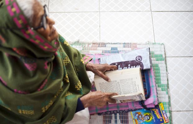 Eine ältere Inderin liest ein Buch auf dem Balkon des Ma Dham Ashram in Vrindavan, Indien am 12. Dezember 2011.