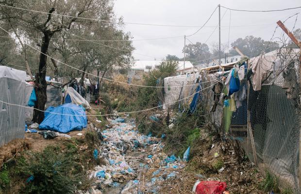 Bach in der Mitte des Lagers gefüllt mit Müll während Starkregen. - Moria ist das größte Lager für Geflüchtete in Europa. Auf der griechischen Ägäisinsel Lesbos wurde ein so genannter Hotspot eingerichtet, an dem Asylverfahren bearbeitet und entschieden werden sollen. Nach und nach wird das Camp immer voller und mittlerweile hat sich ein wildes Areal mit kleinen Hütten aus Palletten und Plane gebildet. Zehntausende wohnen und warten hier. Es gibt nur unregelmässig fliessendes Wasser. Schwere Krankheiten gehen um. Im Februar 2020 ist die Lage besonders prekär.