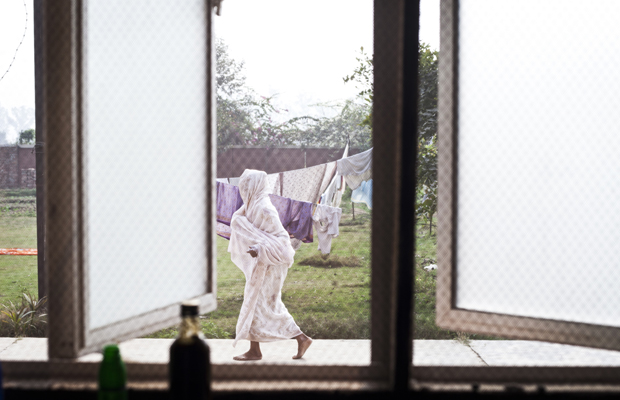 Eine indische Witwe geht durch den Garten des Ma Dham Ashram an einem offenen Fenster vorbei, am 9. Dezember 2011 in Vrindavan, Indien.