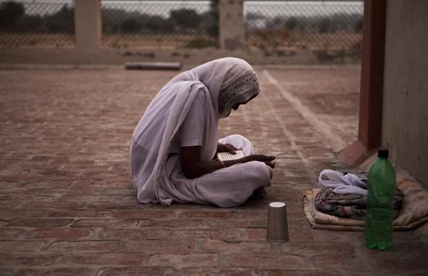 Eine Bewohnerin des Ma Dham Ashrams sitzt auf dem Dach und betet in der Abenddämmerung in Vrindavan, Indien am 5. Juni 2013.