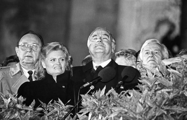 Nach oben schaut Bundeskanzler Helmut Kohl am 3. Oktober 1990 wahrend der Feier zur Wiedervereinigung Deutschlands am Berliner Reichstag mit Aussenminister Hans-Dietrich Genscher, Hannelore Kohl und Bundespraesident Richard von Weizsäcker am 03. 10.1990. Dieses Bild erhielt beim World Press Photo Award 1991 einen Preis.