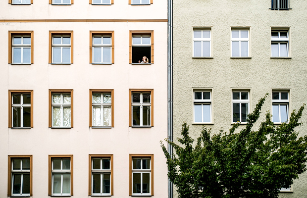 A woman siting a window smoking a cigarette in the Covid-19 summer in Berlin-Mitte.