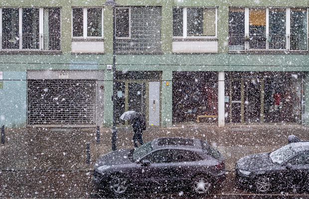 A man walking through a street during the coronavirus lockdown in Berlin, while a woman in a window watches the snow.