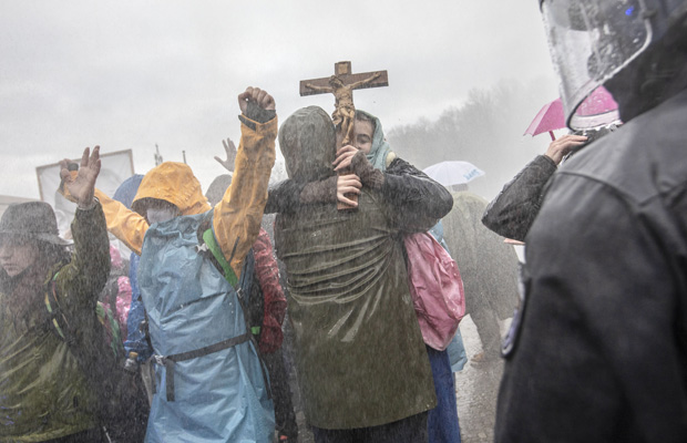 A protester holds a cross while embracing another as people demonstrate against the coronavirus restrictions near the Brandenburg Gate in Berlin, Germany, November 18, 2020. Several thousands participants, among them corona-skeptics, anti-vaccination activists, Querdenken (lateral thinkers) movement supporters, Gathered in several locations at the German capital's government district in protest of coronavirus restrictions. German police officers have contained the demonstration near the Brandenburg Gate, where they used water canon trucks to push the protesters back and disperse them.