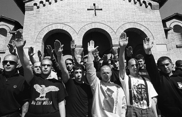 "ITA, ITALY, Predappio, 28.04.2002 Neo fascists with Nazi salute in front of the San Cassiano Cemetery in Predappio. Predappio, near Bologna, is the birth place and burial place of Benito Mussolini, leader of the Italian Fascism, ""Il Duce del Fascismo"". Every year at the day of the death of Mussolini neo fascist and other right-wing radicals rally together on their pilgrimage to this fascist shrine and popular tourist site. Fascism, Neo-Fascism, Skinheads, Fascist Symbol, right-wing radicalism, Far Right, Europe, Italy, Neofascist, extreme right, radical, right wing, rightwing, neo-nazism, neo-fascism, nationalism, Politics, neofacism, racism. Rechte Gruppe, Symbol, Symbolbild, Symbolfoto, symbolisch, Faschismus, Nationalismus, Neofaschismus, Rechtsradikal, Extremismus, Rechtsradikalismus, Neo-Faschismus, Faschisten, Nazi, Nazis, Neonazis, Neonazi, Neonazismus, rechts, Rechte Gruppierung, rechtspopulismus, rechtsextrem, Rechtsextremist, Rechtsextreme, Rechtsextremisten, Rechtsradikalismus, Politik, Europa, Italien"