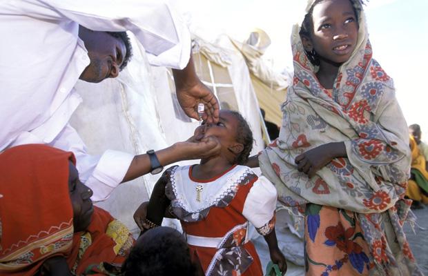 """ERI, Eritrea, Dresa, 23.12.2001 Arzt gibt Kind eine Polio Schluckimpfung im Rahmen des Gesundheitsprogramm """"Kick Polio out of Eritrea"""". Im Ort Dresa siedeln sich ehemals eritreische Fluechtlinge an, von denen viele bis zu ueber 30 Jahren Exils in Camps im Sudan verbrachten. Die Rueckkehr, organisiert von der UN Fluechtlingsorganisation UNHCR und den lokalen Behoerden, umfasst eine der aeltesten Fluechtlingsgemeinden der Welt. Afrikanisch, Dritte Welt, Gesundheit, Gesundheitswesen, Therapie, Entwicklungshilfe, Horn von Afrika. Dieses Bild erhielt beim World Press Photo Award 2002 in der Kategorie Wissenschaft & Technik, Singles, den 3. Preis"""