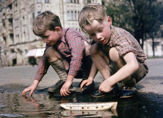 Zwei Jungen spielen mit einem Spielzeugschiff an einer Pfütze auf einer Straße in Berlin, aufgenommen um 1957. Foto: Berliner Verlag / Archiv