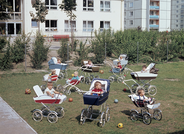 Kleine Kinder sitzen in Kinderwagen auf dem Hof einer Kinderkrippe in einem Neubauviertel mit Plattenbauten, aufgenommen in den 1970er Jahren. Foto: Berliner Verlag / Archiv
