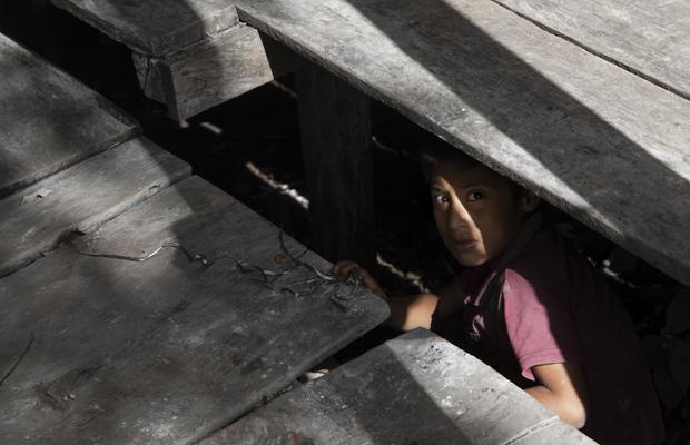Ein kleiner Junge schaut unter einem Holzfußboden hervor. La Limonada gilt als der größte Slum in Lateinamerika. Über 60 000 Menschen leben hier unter schwierigen Bedingungen. 09.02.2020, La Limonada, Guatemala City, Guatemala.